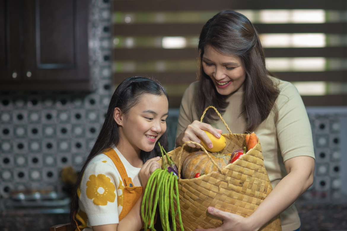 A little girl and a mom happily looking at their basket of fresh produce
