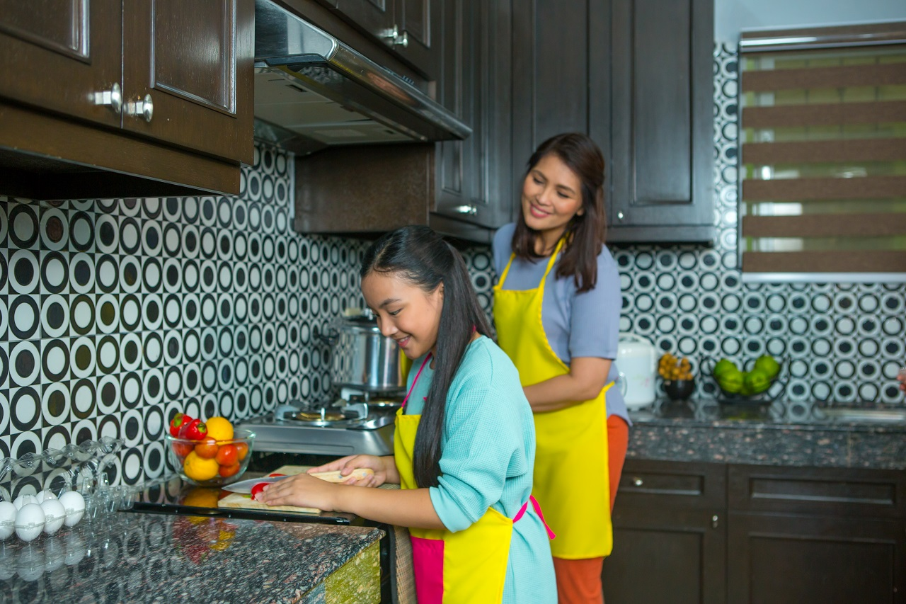 Mother and daughter chopping vegetables