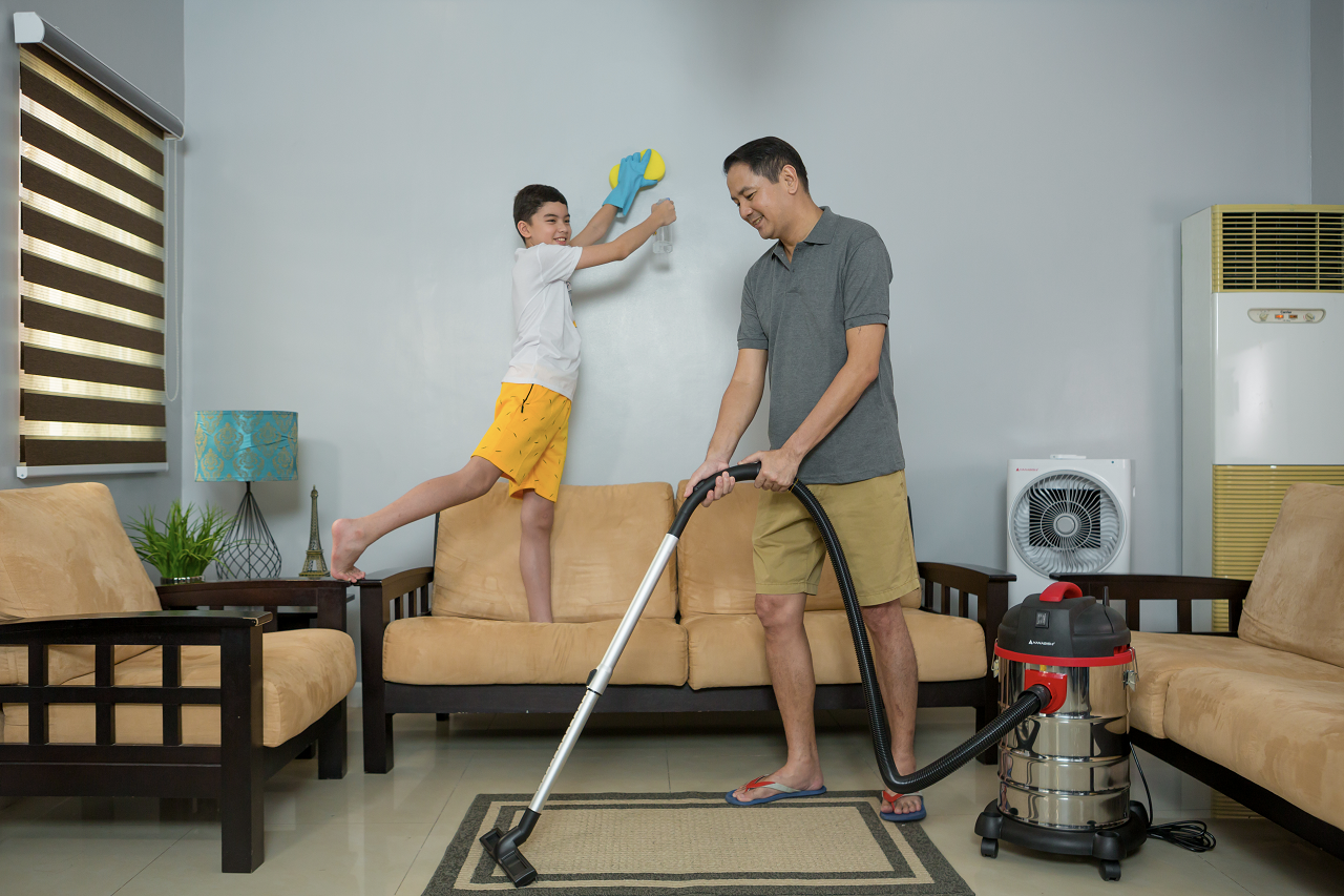 Father and son cleaning their living room