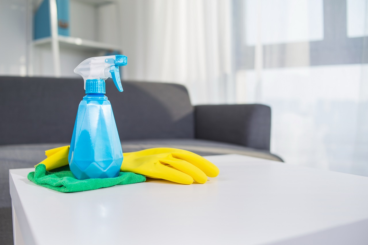 Cleaning spray, gloves, and a rag on a tabletop
