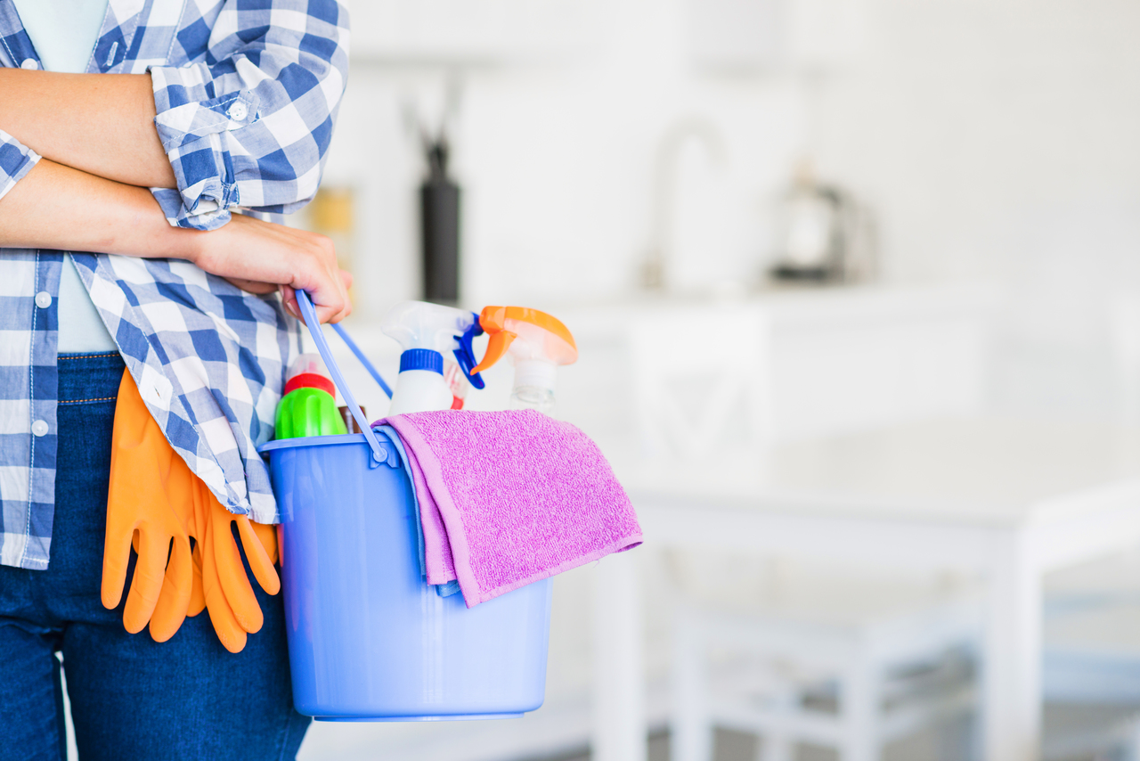 A mom holding house cleaning supplies