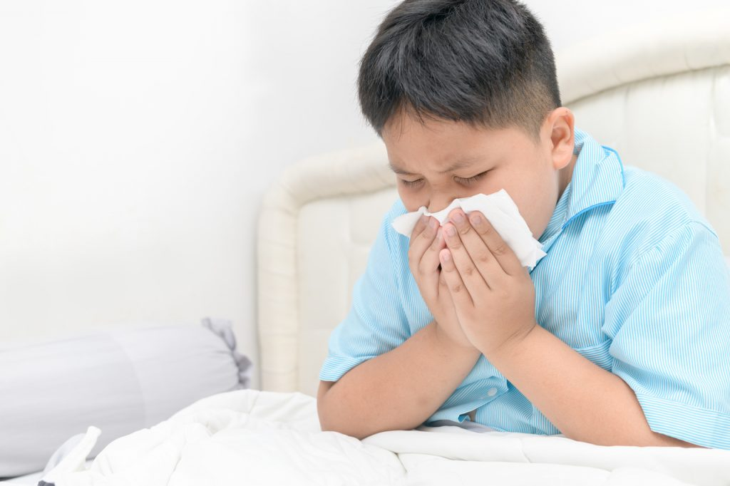 A little boy sneezing because of allergies caused by dust