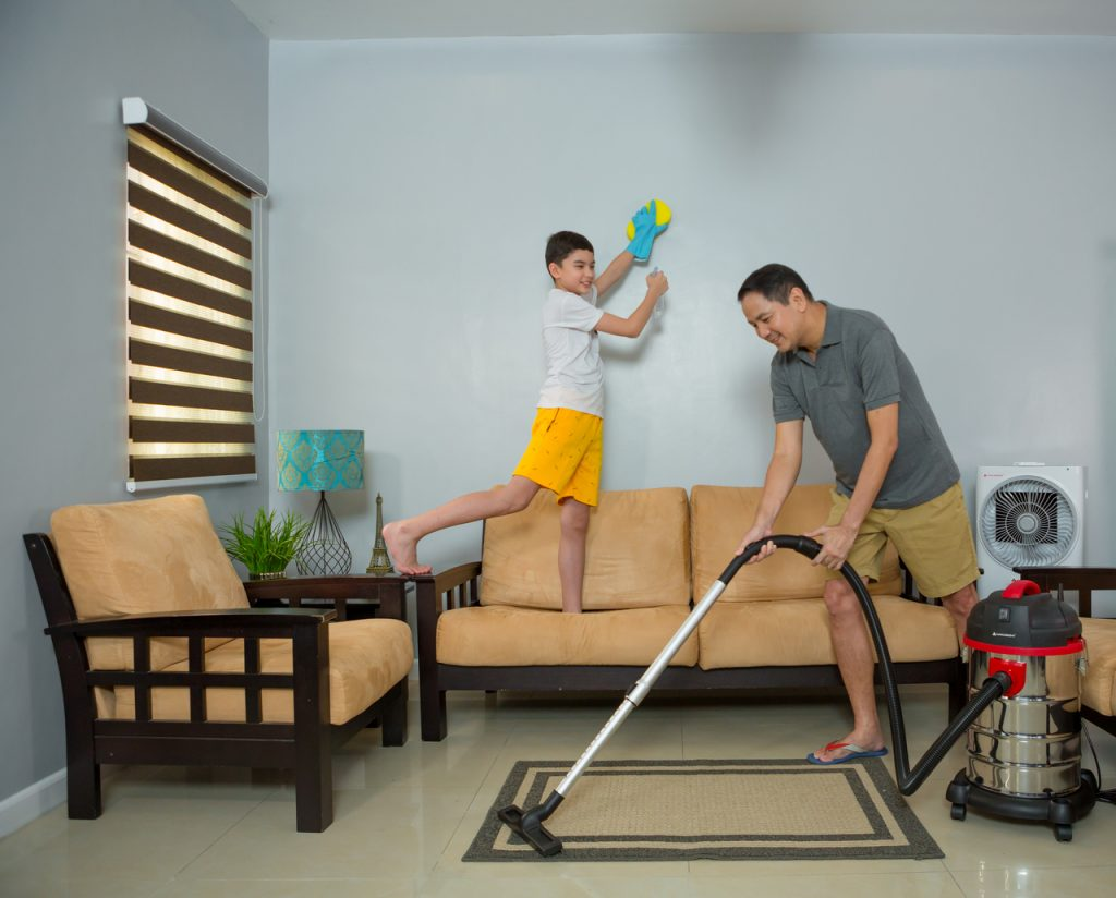Father and son clearing the living room of dust
