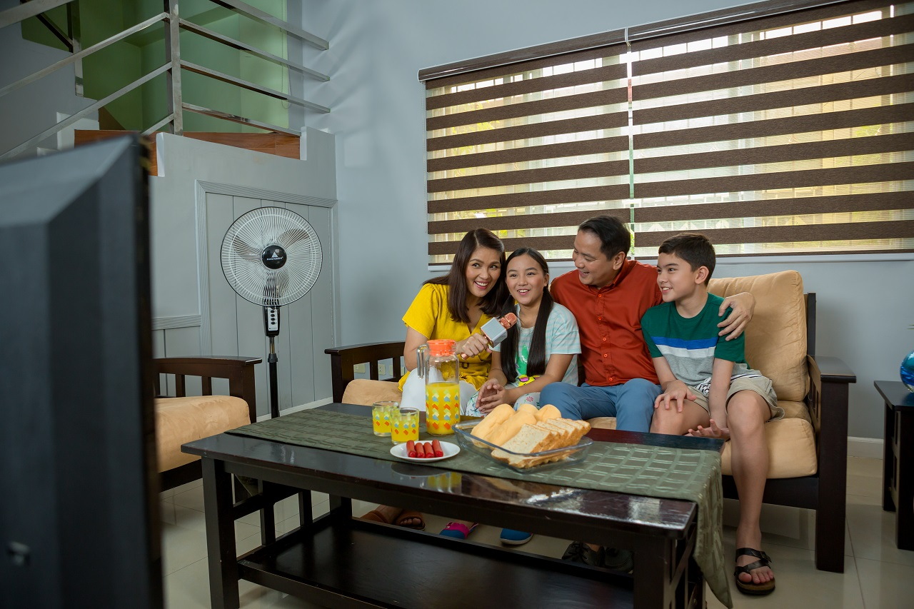 A family singing karaoke in their living room with a fan