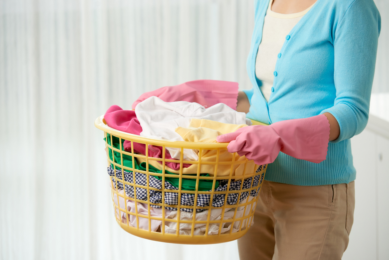 A mother wearing gloves holding a basket of dirty clothing