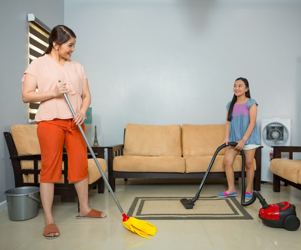 A mother and daughter cleaning their living room