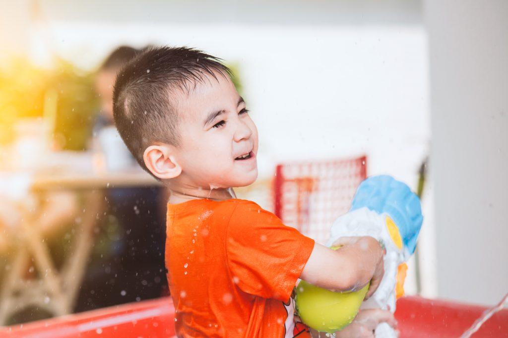 A little boy playing backyard water games