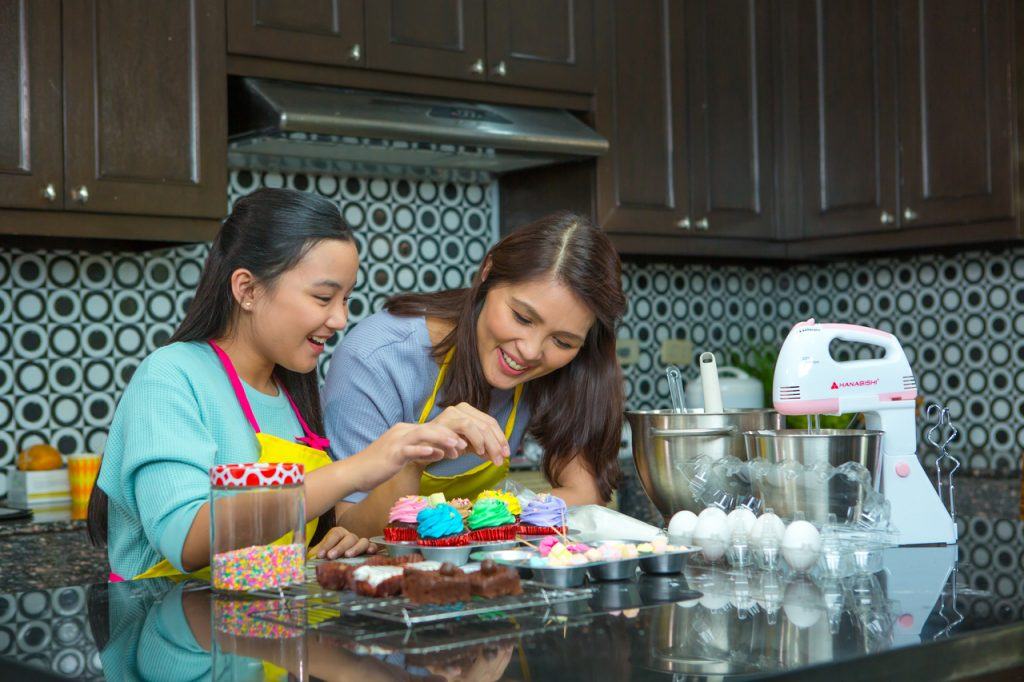 A mother and daughter baking cupcakes