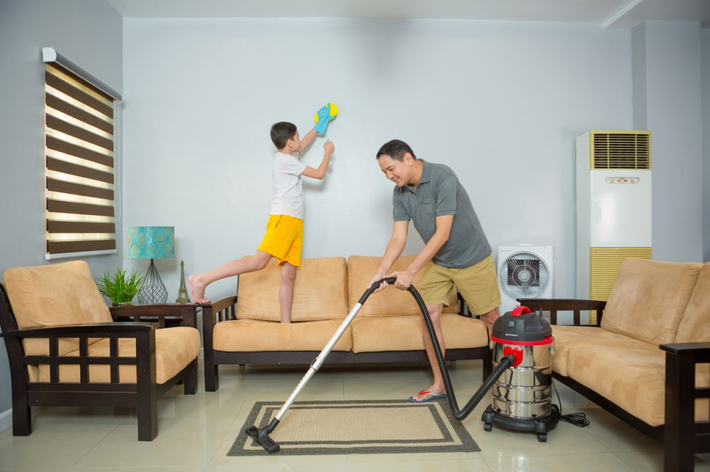 A father and son cleaning the living room