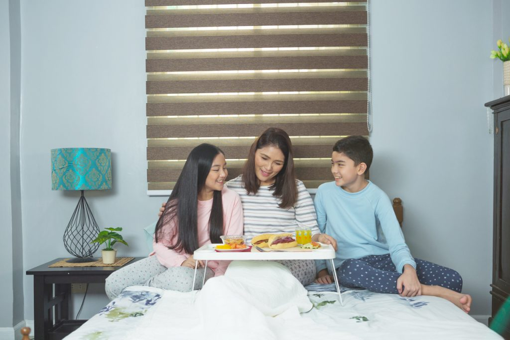 Children surprising mom with breakfast in bed